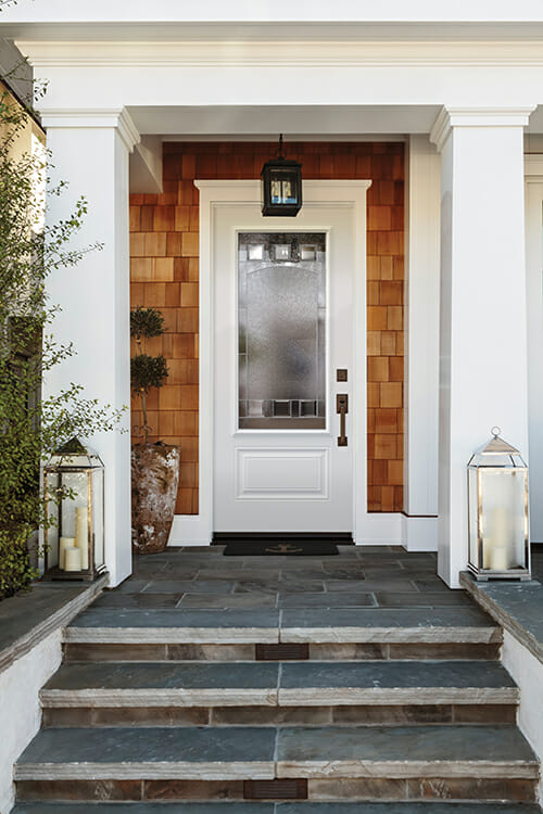 A white front door of a luxury home. The home is naturally stained wood shingles. The door is flanked by two white columns. Also seen is a stone porch and steps.